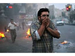 Passersby are overcome by the fumes from burning shithead in the streets of Tehran.